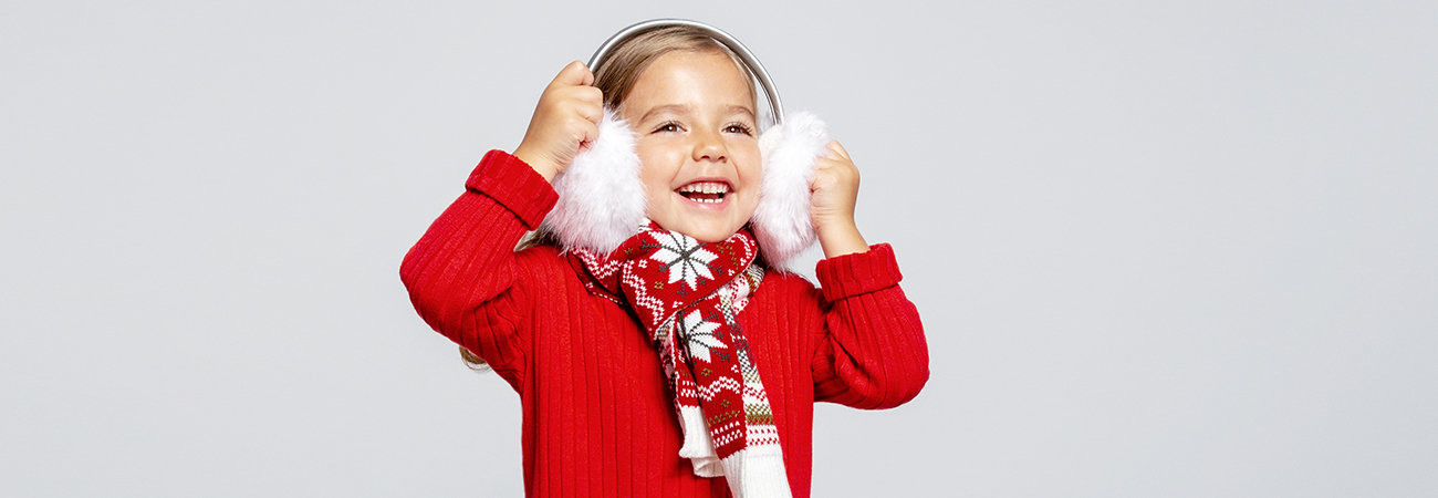 Young girl wearing earmuffs, a scarf, and a red sweater