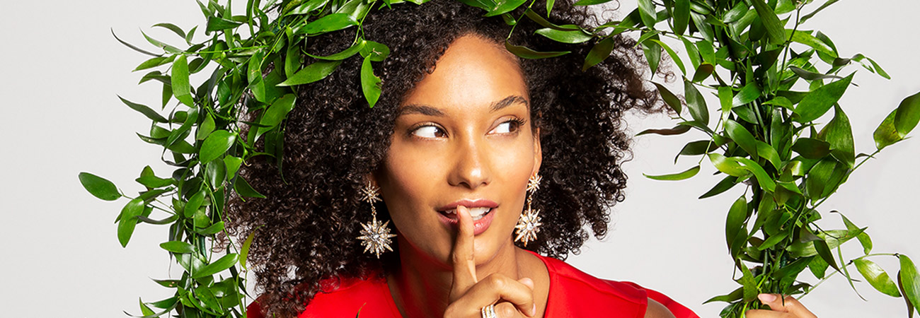 Woman looking through a holiday wreath wearing starburst earrings and holding her finger up to her mouth