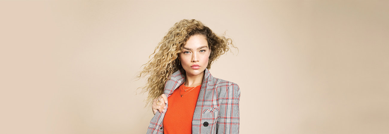 Young woman wearing an orange sweater and plaid jacket