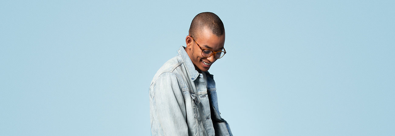 Smiling young man wearing a denim jacket and tortoiseshell glasses