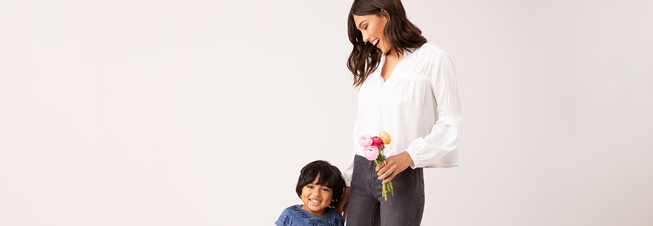 Mom holding bouquet of flowers with her young son