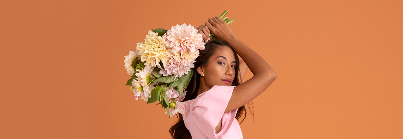 Woman wearing a pink dress holding a bouquet of flowers above her head against an orange background