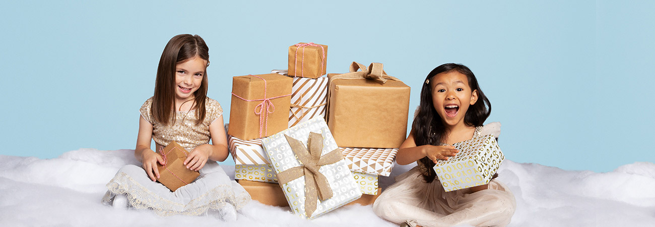 Two little girls sitting by a pile of presents in the snow