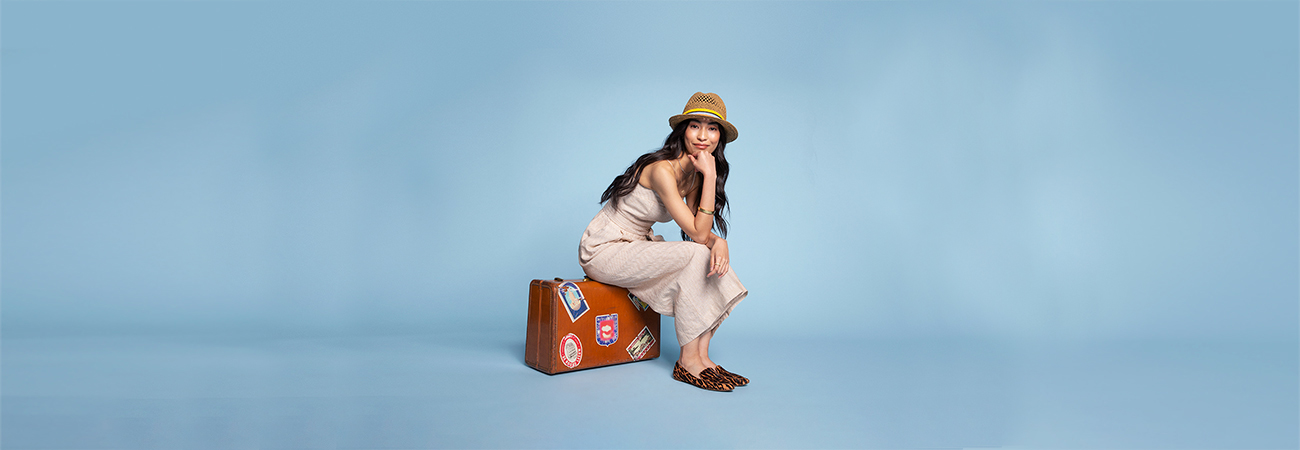 Woman wearing a straw hat and jumper sitting on a suitcase