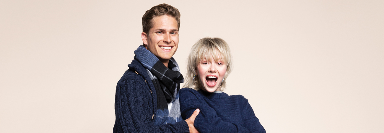 Smiling young man and woman wearing matching blue sweaters