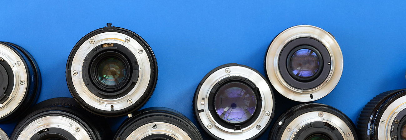 Camera lenses arranged on a blue background
