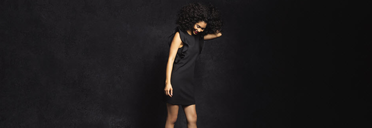 Female model in sleeveless black slip dress