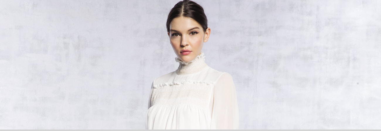 Female model in lacy white high-collared blouse