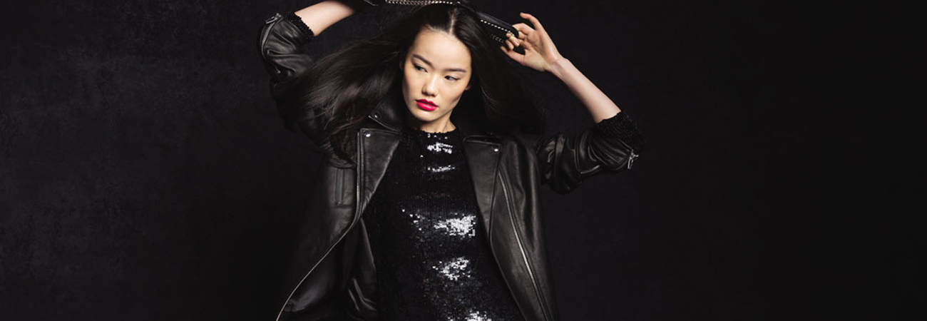 Female model wearing a black sequined dress and black leather jacket