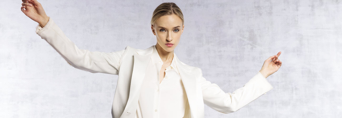 Female model wearing a white blazer and blouse and striking a pose