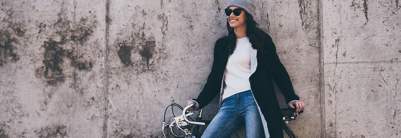 smiling woman in sunglasses and casual clothes stands with her bike against a concrete wall