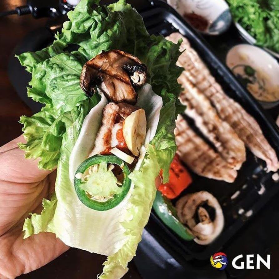 Gen Korean BBQ lettuce wrap with vegetables and meat. Background of photo shows meat on grill.