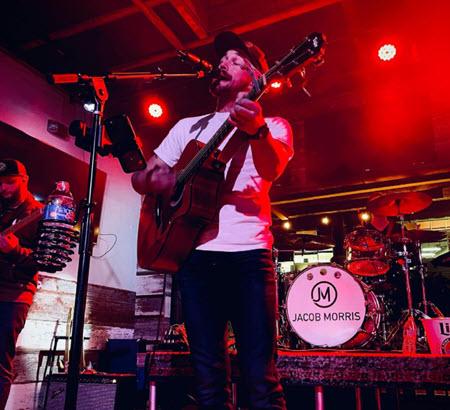 man playing guitar singing with band