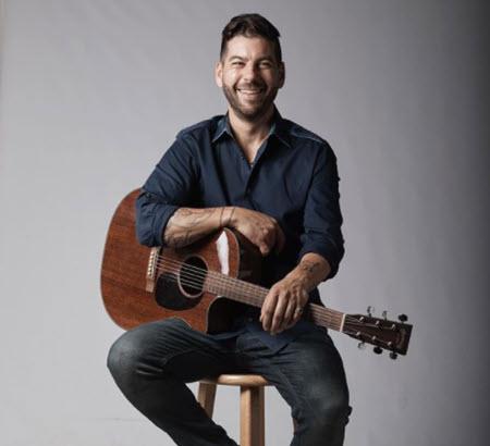 man holding guitar sitting on stool