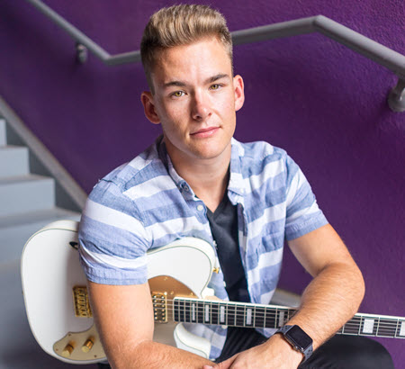 man sitting in front of a purple wall holding a guitar