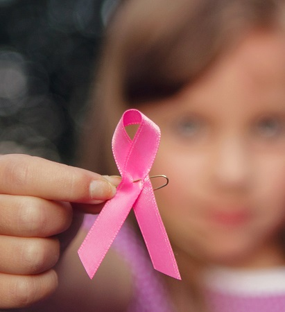 Young girl holding pink ribbon.
