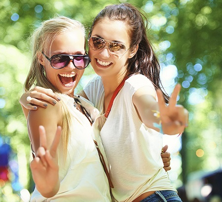 Two girls in t-shirts, standing outside, holding up a peace sign with their hands.