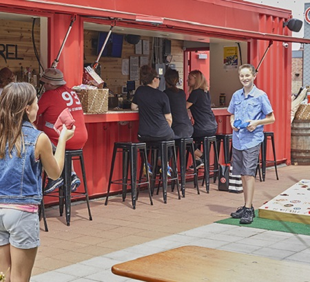 Kids playing corn hole outside, next to a beer garden.