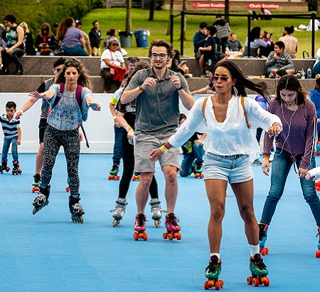 Group of men, women and kids, skating at an outdoor roller rink.