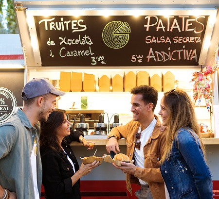 Two couples standing in front of a food truck window, with food in their hands, talking with each other and laughing.