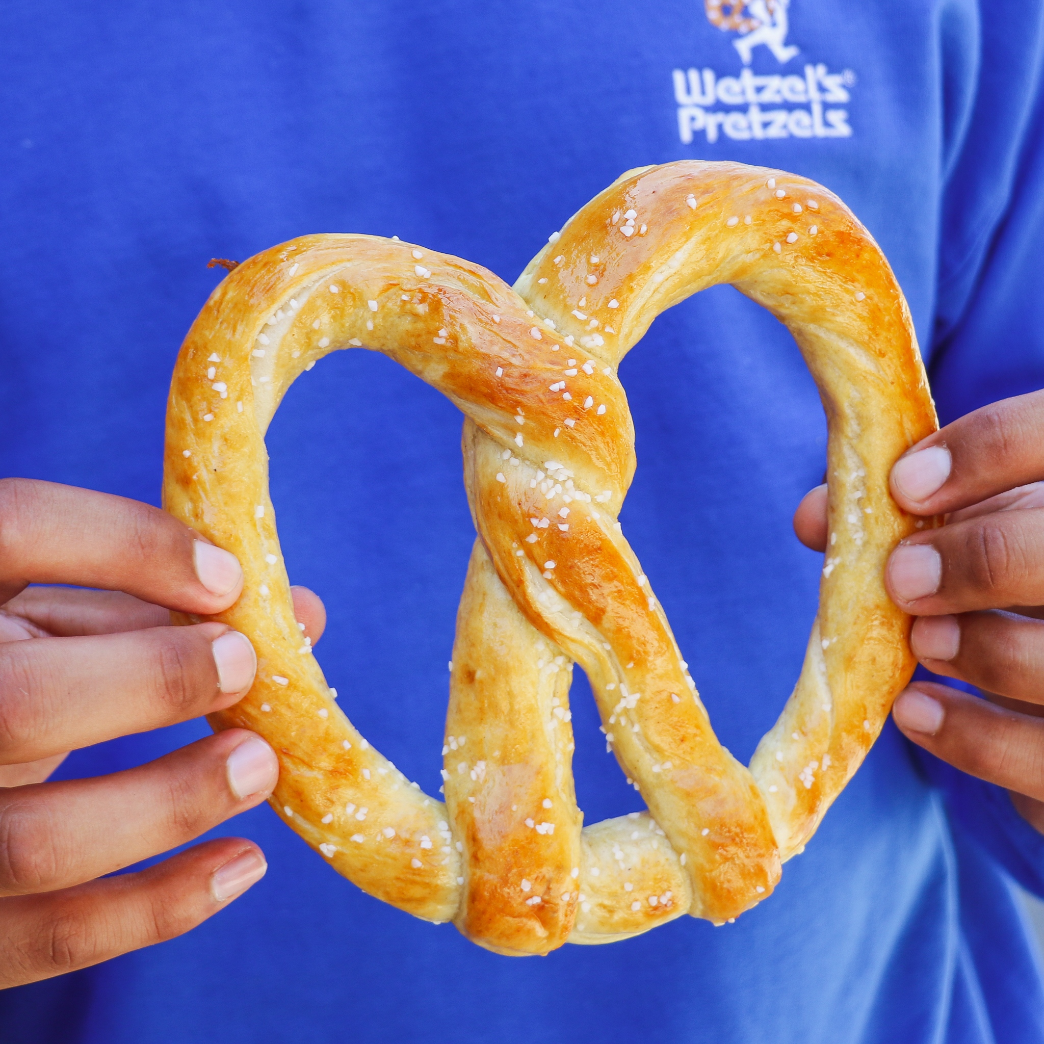 Person wearing a Wetzels Pretzel t-shirt holding a pretzel