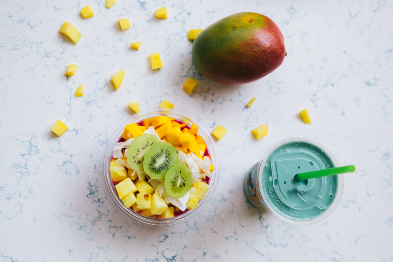 Playa bowl with Kiwi, pineapple, mango and other fruit, a blue/green smoothie, a whole mango and mango pieces