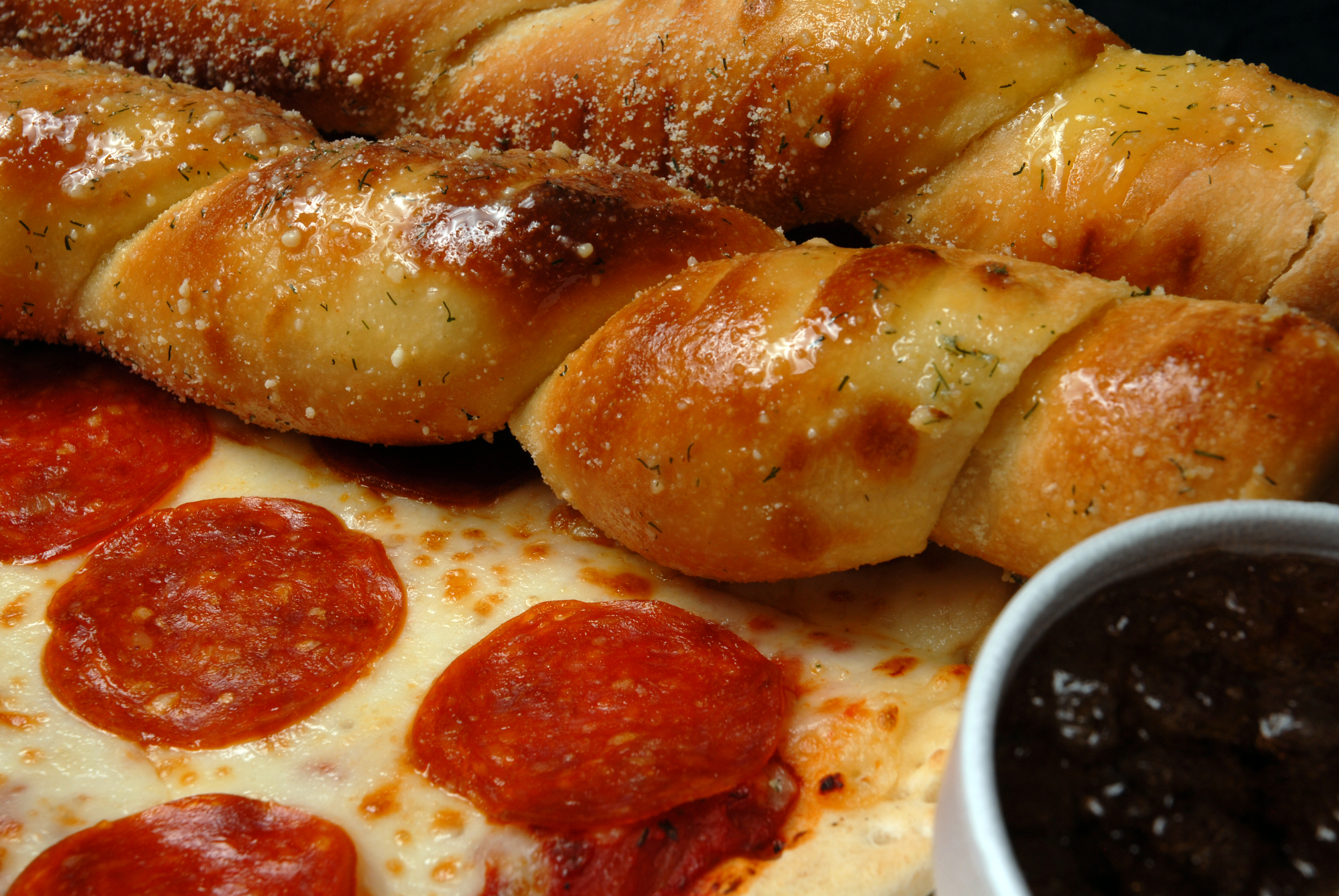 Pizza and bread sticks with sauce