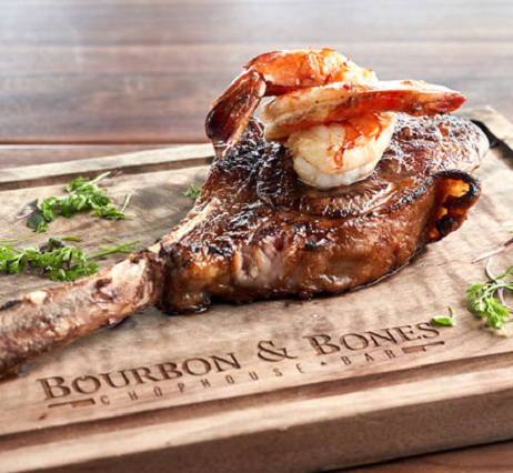 Tomahawk steak garnished with shrimp on a wooden chopping block.
