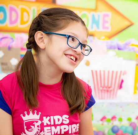 Little girl wearing glasses and smiling with party decorations in the background.