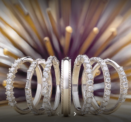 Gold plated rings with diamonds lined up on a display board.