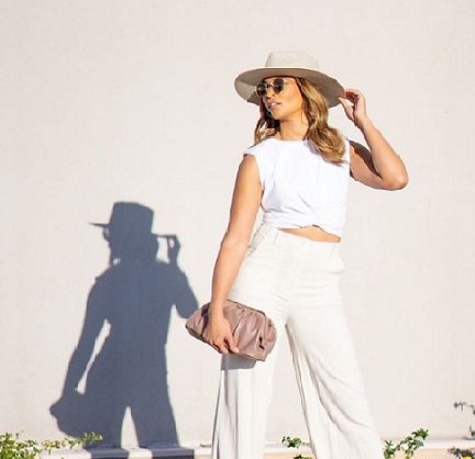Woman in white flowing clothes with a handbag posing in the sun.