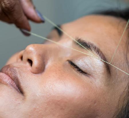 Woman having her eyebrows threaded