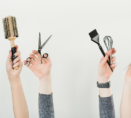 Hands holding a hair brush, sheers, and hair coloring tools.