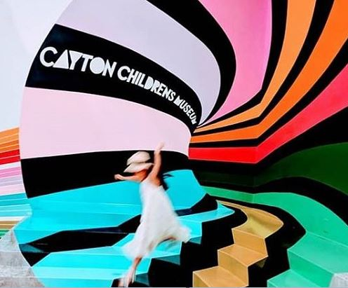 Rainbow optical illusion wall which Cayton Children's Museum logo
