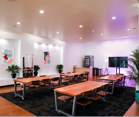 tables and chairs in meeting room with fridge and tv