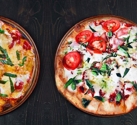 Two pizzas with basil and tomatoes