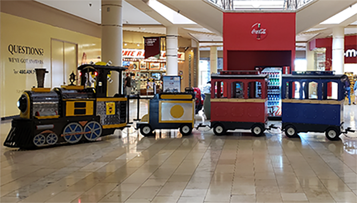 Train on tile floor at the mall with the words LensCrafters and Kay Jewelers in the background