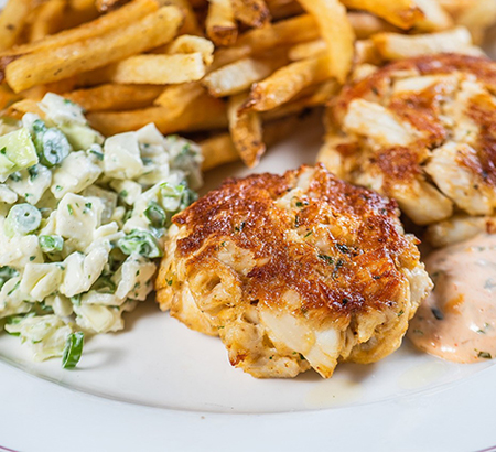 crab cakes, coleslaw, and french fries on a white plate