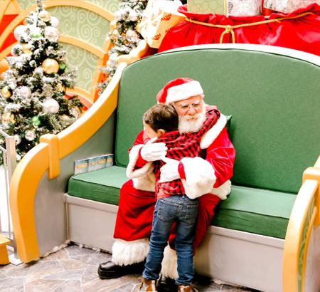 Girl sitting with Santa at Santa HQ set.