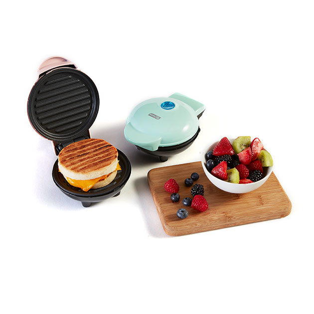 Compact panini presses and a small cutting board with a bowl of fruit