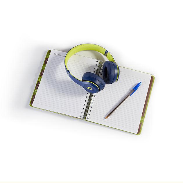 Wireless headphones and a pen resting on a notebook