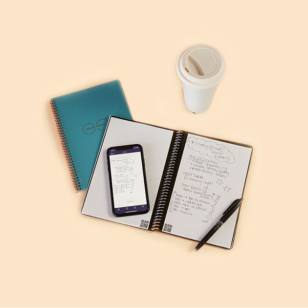 Notes in a notebook, along with a phone and coffee cup