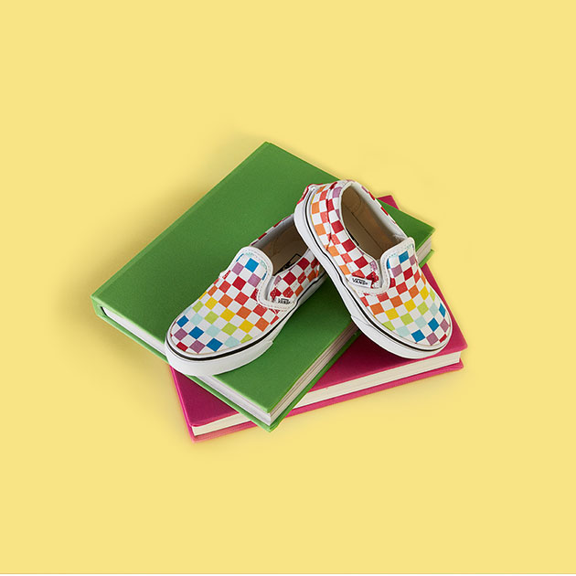 Pair of rainbow checkerboard Vans shoes on a stack of books