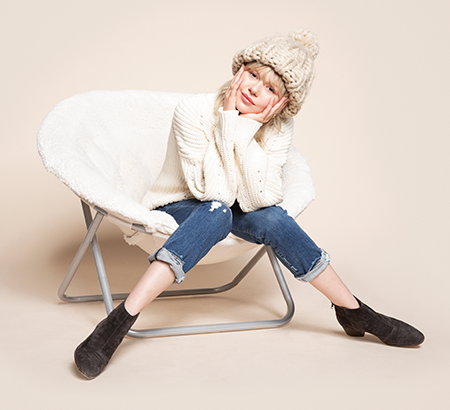 College aged girl sitting in a round chair and wearing a knit sweater, beanie, and rolled up jeans