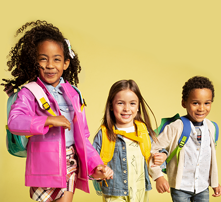 Three elementary school aged children locking arms and dressed in fun clothes against a yellow background.
