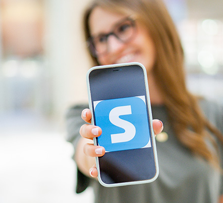 A young woman holding up her phone screen with Shopkick on it.
