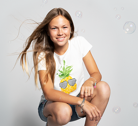 Teenage girl wearing summery t-shirt and shorts surrounded by bubbles