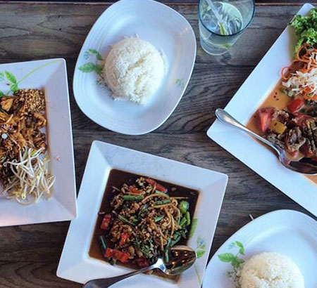 Three Thai dishes including two plates of white rice.