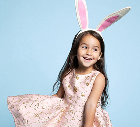Smiling young girl wearing a bunny ears headband and spring dress