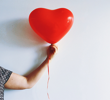 An arm holding a red heart balloon